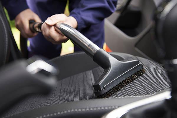 image of someone vacuumingvinyl car seats